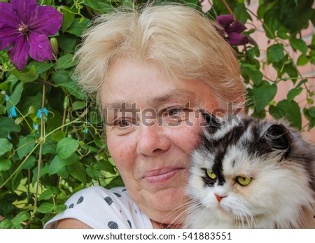 Housewife and her pet cat in the garden