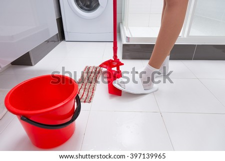 Housewife changing the cloth on the colorful red mop operating the lever with her foot as she cleans the bathroom floor