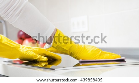 Housewife cleaning an induction plate, closeup shot - stock photo