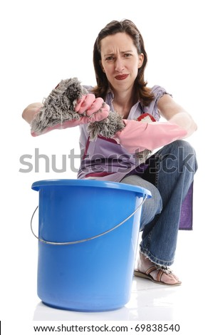 Housewife, cleaning lady with long dark blond hair and apron with the housework isolated on a white background. She is wringing out the cloth on the mop bucket. - stock photo