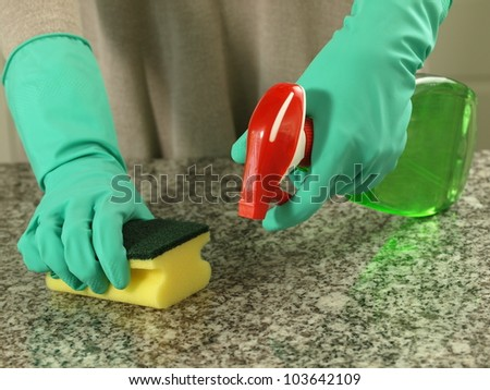Housewife cleaning up a kitchen top with sponge and spray - stock photo