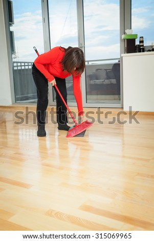 Housewife dusting wooden floor with red broom