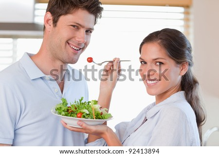 Housewife feeding her husband in their kitchen - stock photo