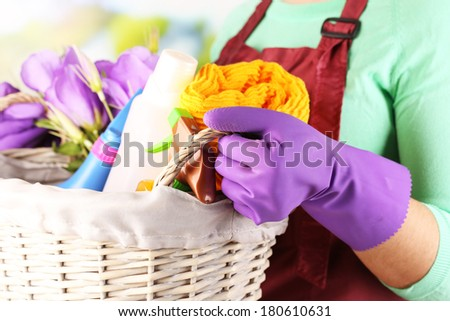 Housewife holding basket with cleaning equipment on bright background. Conceptual photo of spring cleaning.  - stock photo