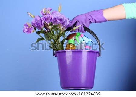 Housewife holding bucket with cleaning equipment on bright background. Conceptual photo of spring cleaning.  - stock photo