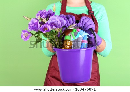 Housewife holding bucket with cleaning equipment on color background. Conceptual photo of spring cleaning.  - stock photo