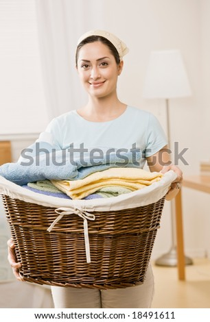 Housewife holding full basket of laundry - stock photo