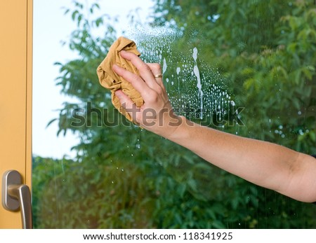 Housewife is cleaning a window - stock photo