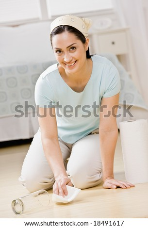 Housewife kneeling in bedroom wiping up spilled water with paper towel - stock photo