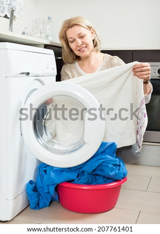 housewife looking at  clothes near washing machine at  home