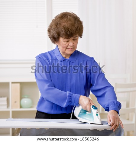 Housewife performing chore of ironing laundry