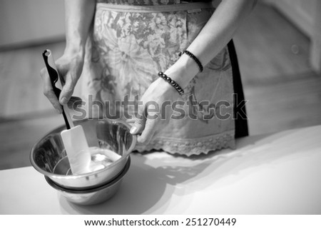 Housewife's hands kneading the dough for baking, monochrome - stock photo