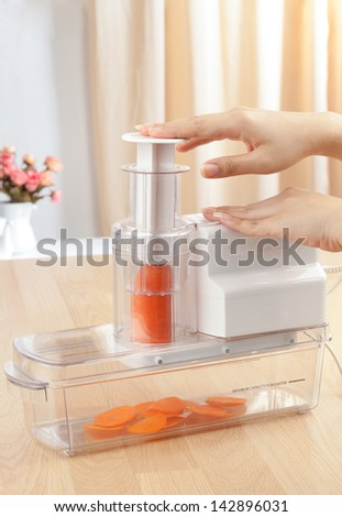 housewife's hands slicing carrot by electric slicer machine