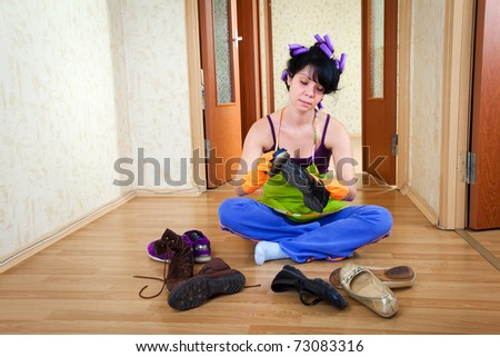 housewife sits on a floor and cleans footwear - stock photo