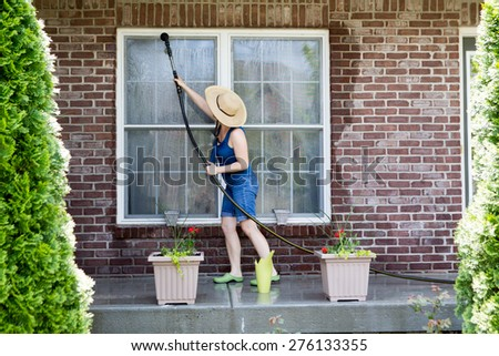 Housewife standing on a patio washing the windows of her house with a hose attachment as she spring-cleans the exterior at the start of the new spring season - stock photo