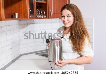 Housewife stands near white countertop with steel electric tea kettle in hands, copy space - stock photo