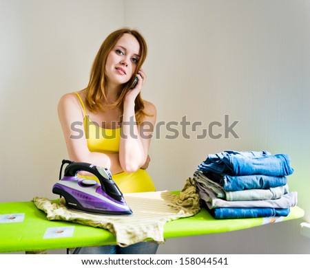 Housewife talking on the phone while ironing on grey background  - stock photo