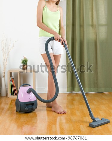 Housewife using vacuum cleaner machine to clean the floor - stock photo