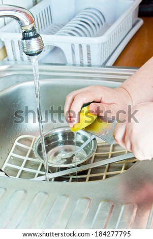 Housewife washing dishes with sponge in kitchen sink