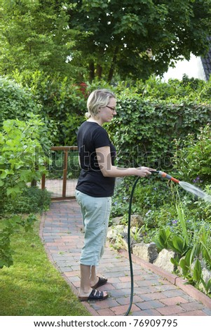 housewife watering the flowerbed.. - stock photo