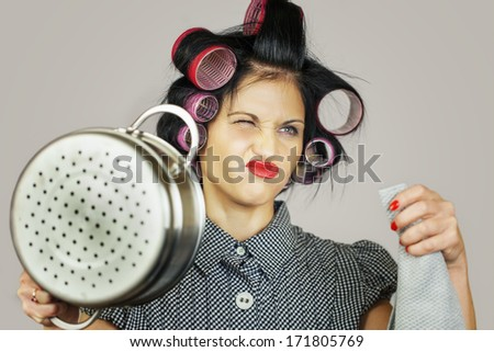 Housewife with a kitchen pot on grey background - stock photo