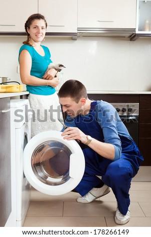 Housewife with cat  watching as worker repairing washing machine - stock photo