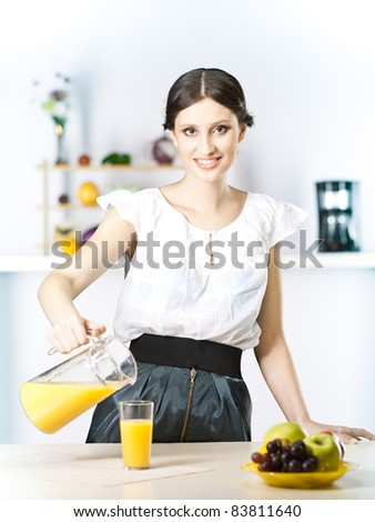Housewife with orange juice jar and fruits in the kitchen - stock photo