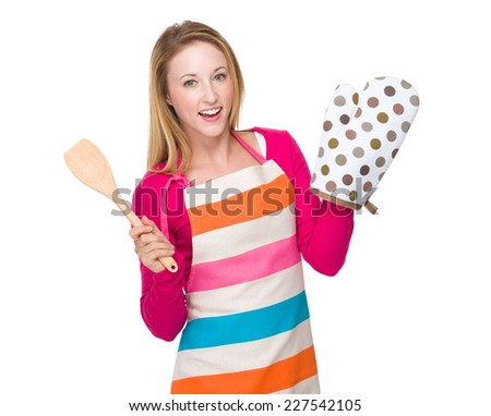 Housewife with oven gloves and wooden turner - stock photo