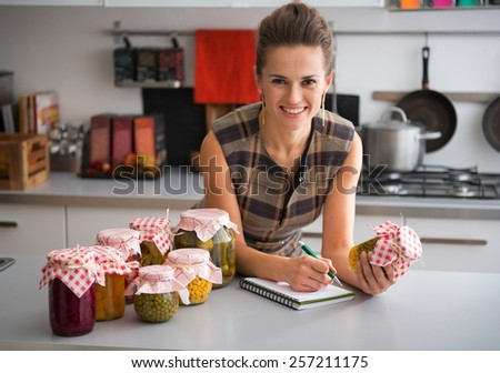Housewife writing in notepad among jars of pickled vegetables in kitchen