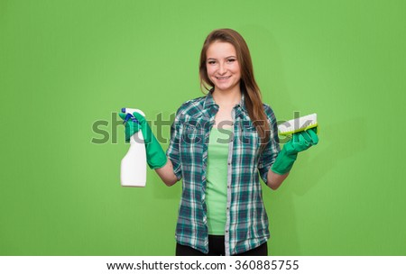 Housework and housekeeping concept.Cleaning woman with cleaning spray bottle, brush and gloves happy and smiling. Beautiful cleaning girl isolated on green background with copyspace. Mixed race woman. - stock photo