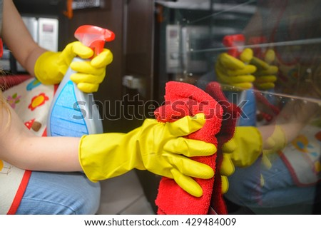 housework and housekeeping concept - close up of woman hand in gloves - stock photo