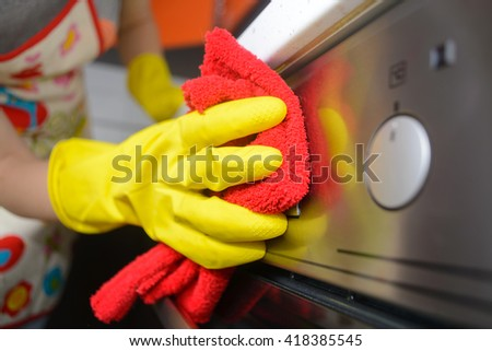 housework and housekeeping concept - close up of woman hand in p - stock photo