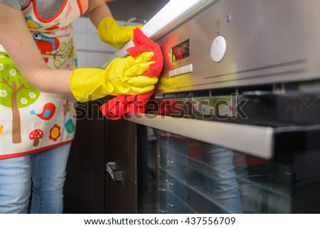 housework and housekeeping concept - close up of woman hand in protective gloves cleaning oven surface by red cloth. - stock photo