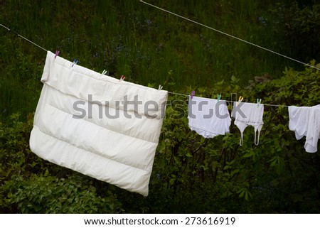 Housework. Clean wet laundry bedding hanging to dry on the line clothesline outdoor. Rural scene. - stock photo