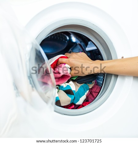 Housework: Detail of Female Doing Laundry, while Putting Colorful Clothes into the Laundry Machine