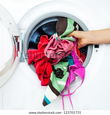 Housework: Detail of Female Doing Laundry, while Putting Colorful Clothes into the Laundry Machine - stock photo