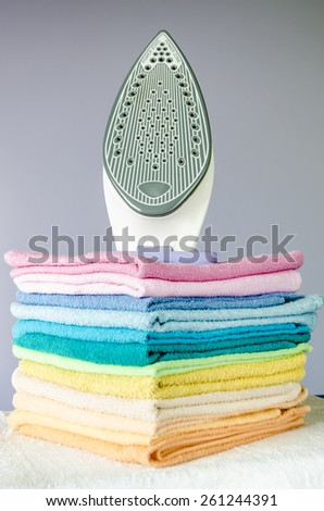 Housework, ironing iron colorful towels on the ironing board. - stock photo