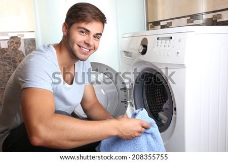 Housework: Man loading clothes into washing machine - stock photo