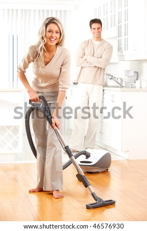 Housework, vacuum cleaner, young couple, home, kitchen - stock photo