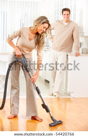 Housework, vacuum cleaner, young couple, home, kitchen. Housework