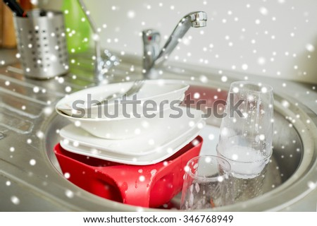 housework, washing-up and housekeeping concept - close up of dirty dishes washing in kitchen sink over snow effect - stock photo