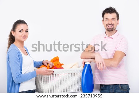 Housework. Young woman and man are doing laundry and looking at the camera. - stock photo