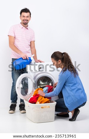 Housework. Young woman and man are doing laundry with washing machine at home.