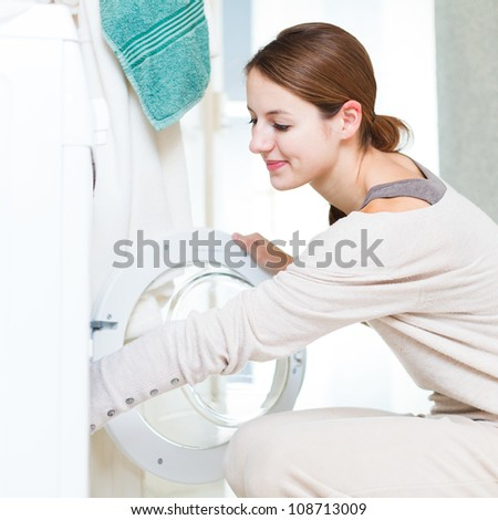 Housework: young woman doing laundry (shallow DOF; color toned image) - stock photo
