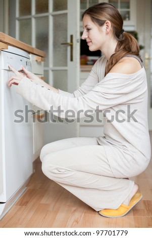 Housework: young woman using a dishwasher - stock photo