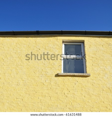 Housing Concept View of Abstract Architectural Detail of a Window, Brick Wall and Blue Sky Above - stock photo