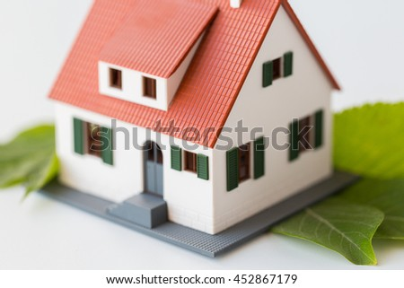 housing, environment and ecology concept - close up of living house model and green leaves - stock photo