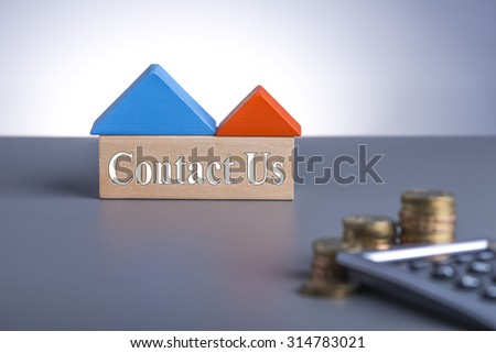 Housing Loan concept. House Wooden Block, coins and calculator with word Contact Us  - stock photo