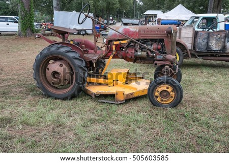 HOUSTON, MISSISSIPPI - September 24, 2016: An antique Farmall tractor that has been modified to use a modern grass cutting attachment.