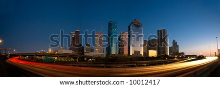 Houston skyline against blue sky after sunset surrounded by lights of highway traffic - stock photo